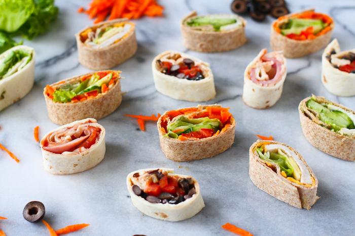 Wraps mit Schinken, schwarzen Oliven, roter Paprika, Karotten, gelbem Käse und grünem Salat