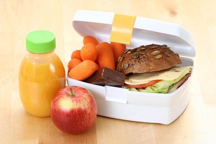weiße Plastikkasten für Mittagessen mit gekochten Karotten, belegtes Vollkornbrötchen mit Käse, grünem Salat und Filet, Schokowaffel, roter Apfel und Orangensaft zum Dessert