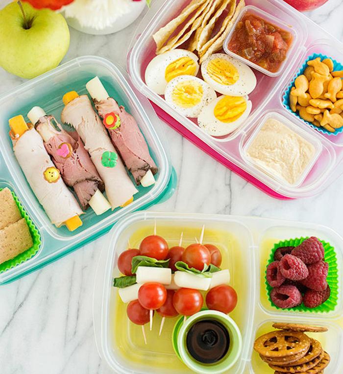 Käsestangen mit Schinken, Schaschliks mit roten Cherrytomaten, Käsestückchen und grünem Salat, runde Kekse, bestreut mit Salz, gekochte und halbierte Eier, weißer Humus und Tomatensoße als Dip für das arabische Brot
