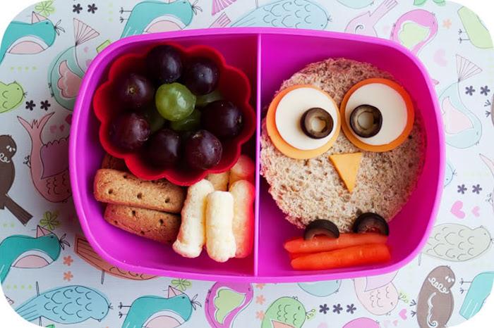 Lunchbox mit zwei Unterteilungen, Butterbrot mit runder Form, Eulengesicht aus zwei Sorten Käse und schwarzen Oliven, drei Minikarotten, Dessertunterteilung: rote und weiße Trauben, Kekse, MArschmallows, Tischdecke mit Vögeln in Pastellfarben