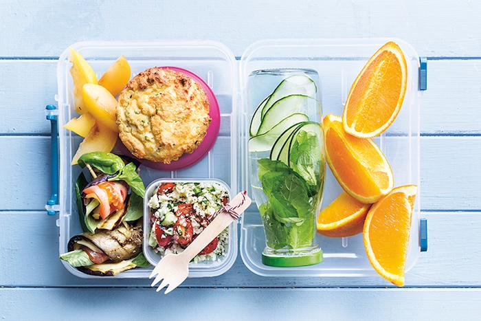 Plastikdose mit gebratenen Auberginen, Tomaten und Spinat, Quinoasalat mit Petersilie und roter Paprika, hausgemachte Kekse mit Honig, Orangen- und Pfirsichstücke, DIY Minz-Gurke-Getränk