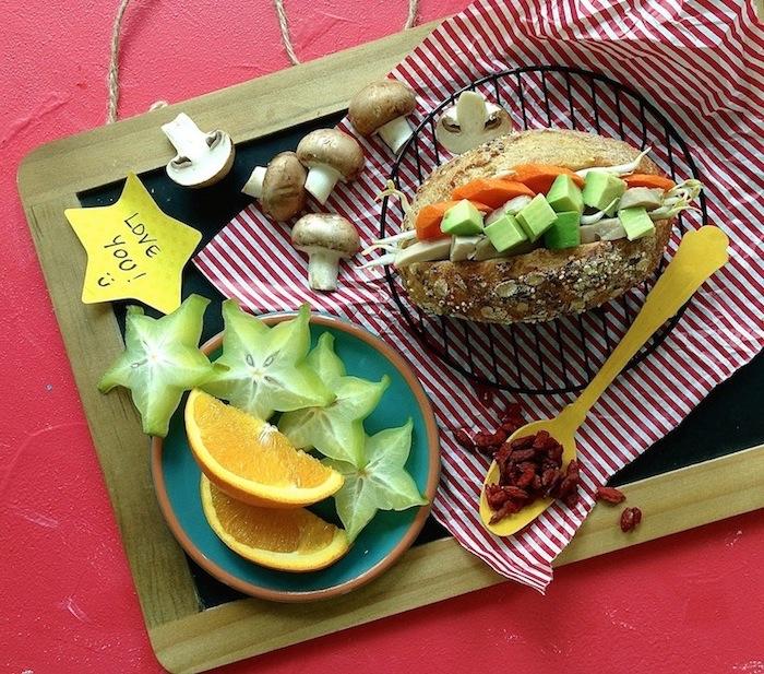 Vollkornbrot mit Sesam, gefüllt mit Karotten, Avokado und Schinken, halbierte Pilze, Gurkenbaum-Früchte, Orange, rote Beeren, Love-You-Zettel