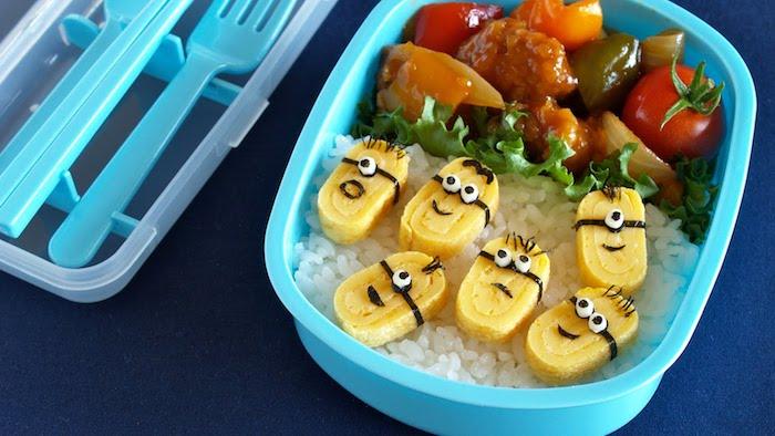 Brotdose mit Plastikbesteck, weißer Reis mit kleinen Stückchen Pfannkuchen, dekoriert mit Minions-Gesichtern, Fleisch mit gekochten Zwiebeln, orangen und roten Cherrytomaten, grüner Paprika und grünem Salat