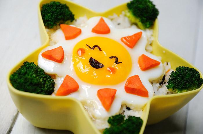 kleine Sonne aus Spiegelei, Reis mit Petersilie und Brokkoliröschen als Beilage, gelber Plastikkasten in der Form eines Sterns