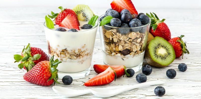 Joghurt im Glas mit drei Sorten von Früchten - Kiwi, Erdbeeren, Blaubeeren, serviert mit Haferflocken, weiß gestrichener Holztisch, zwei kleine Porzellanlöffel