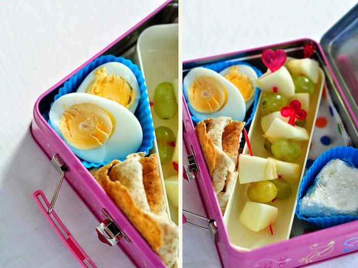 kleine Metallkiste in Lilafarbe, Muffinförmchen aus Silikon, Käse in Frischhaltefolie, Obst-Schaschliks mit weißen Trauben und kleinen Apfelstücken