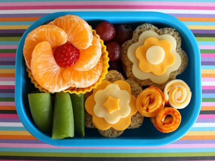 zwei Butterbrote in der Form von Blumen, gelbe und weiße Käse, frisches Obst, bunte Tischdecke mit Streifen in allen Farben