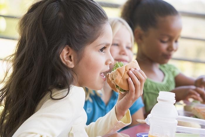 drei kleine Mädchen mit unterschiedlichem Herkunft essen zusammen in der Pause