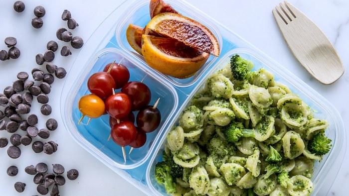 Pasta-Lunchbox mit grünem Pesto und Brokkoli, drei Sorten Cherrytomaten, gebratene Orangen, Schokotropfen, Holzgabel, Holzlöffel