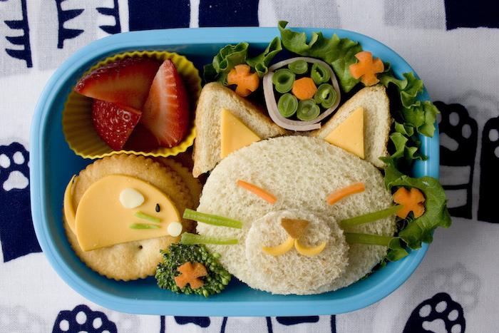 Mittagessen für kleine Kinder: Sandwich in der Form eines Katzengesichts, Schnurrhaare aus grüner Paprika, gewürfelte Erdbeeren, Kekse mit Käse, Tischdecke mit Katzenpfoten-Print