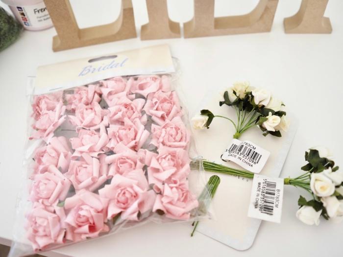 Buchstaben aus Blumen selber machen, Name aus künstlichen rosafarbenen Rosen und MDF