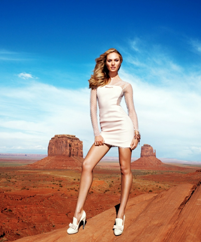 Candice Swanepoel Frisur, dunkelblonde lange Haare, weißes kurzes Kleid mit langen Spitzenärmeln