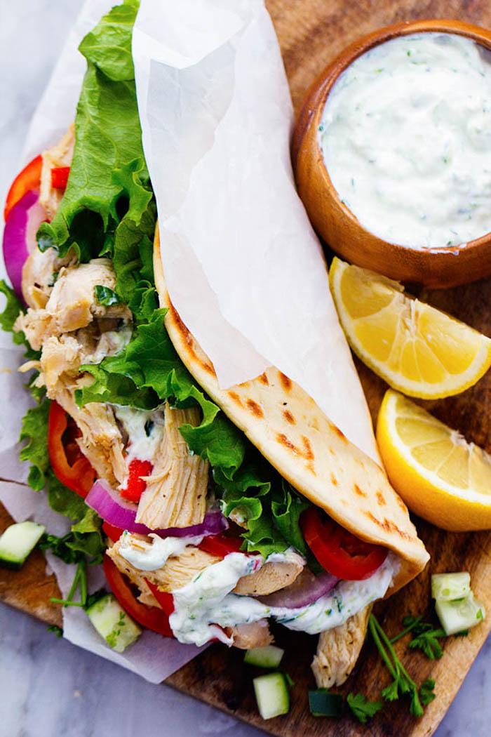 Tortilla Wrap mit Zaziki- Hähnchenfleisch, Tomaten, roten Ziwebeln, Petersilie und grünem Salat, Stücke frischer Zitrone als Dekoration