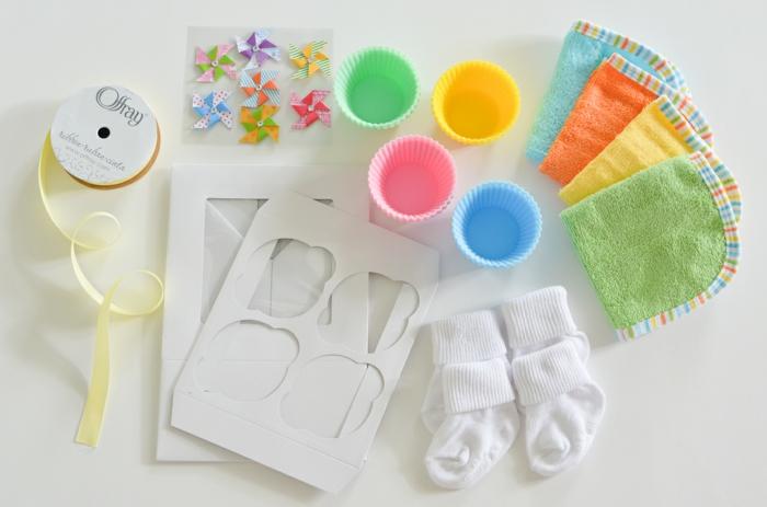 Cupcakes aus Babysöckchen selber machen, bunte Muffinförmchen und gelber Band, Materialien für DIY Projekt