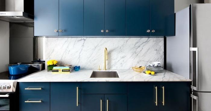 designer küchen, moderne küchenmäbel, dunkelblaue schränke, küchenwand aus marmor, elemente aus messing