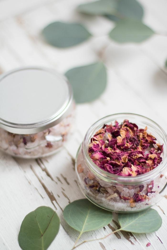 hausgemachtes Badesalz mit Rosenblüten, in kleinem Einmachglas, Rosenblätter daneben