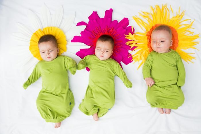 Drei süße Babys verkleidet als Blumen, grüne Kleidung und Kissen als Blüten in Gelb und Violett