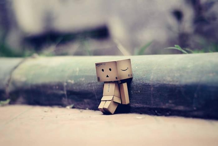 trauriges bild mit einem kleinen traurigen wesen aus karton und grass