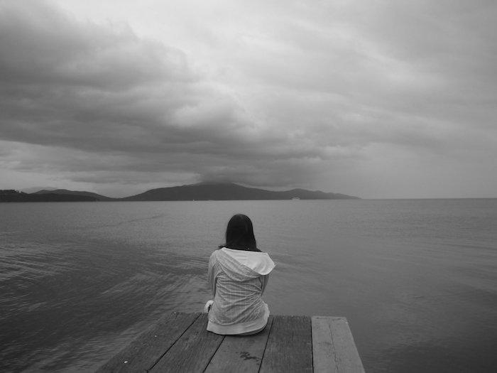 eine junge traurige frau und see und himmel mit grauen wolken - zum thema traurige bilder zum weinen