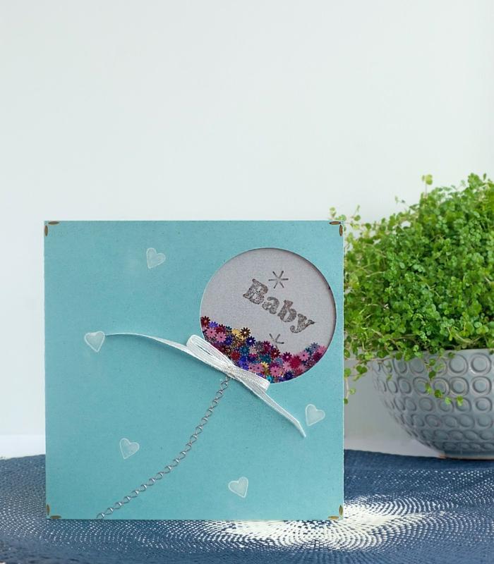 Fotoalbum für Baby selber machen, blauer Umschlag mit kleinen weißen Herzen, bunte Perlen in Luftballon