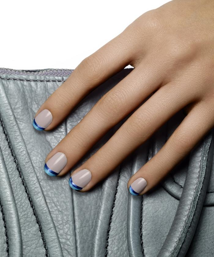 Französische Maniküre in Blau und Weiß, ovale Nagelform, graue Ledertasche als Hintergrund