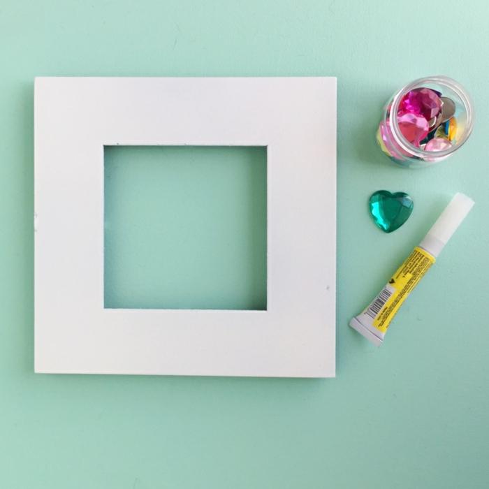 Geburtsgeschenk selber basteln, weißen Rahmen mit Kristallen bekleben, zur Geburt schenken
