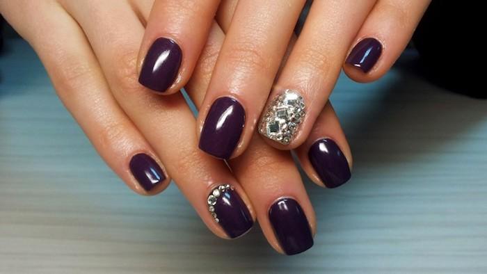 schöne gelnägel dunkellila lackfarbe dekoration auf einem nagel in silberner farbe nageldesign mit steinen