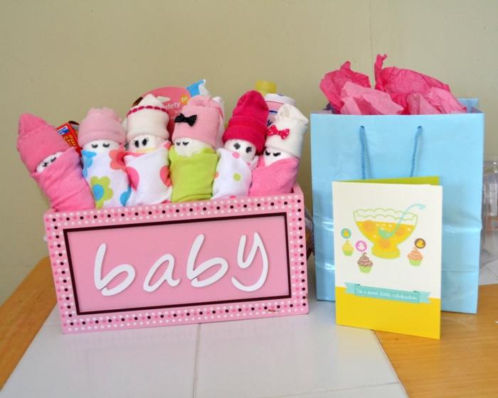 Bunte Tücher und Babysöckchen in Form von Babys, eine Grußkarte mit Cupcakes und Punsch, blaue Verpackung