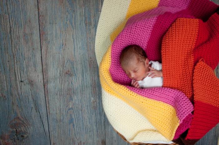 Selbstgestrickte Decke in fröhlichen Farben, süßes schlafendes Baby, Geschenkideen zur Geburt
