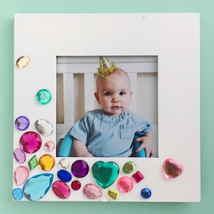 Fotorahmen zur Geburt schenken, bunte Kristallen mit Kleber befestigen, süßes Baby mit Partyhut