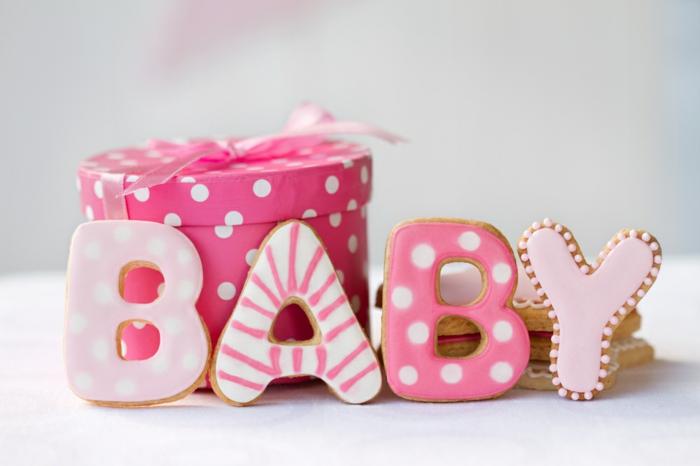 Schöne Geschenkideen zur Geburt, Kekse als Buchstaben, rosafarbene Verpackung mit weißen Punkten und Band