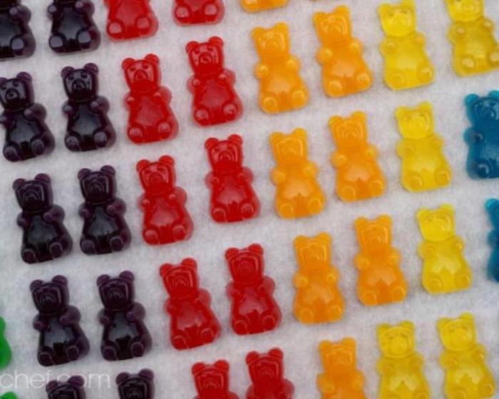 Reihen von Gummibärchen - zwei schwarze, zwei rote, zwei orange und eine gelbe