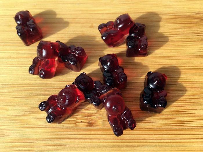 Gummibärchen Rezept - kleine rote Gummibärchen auf einer Arbeitsplatz aus Holz