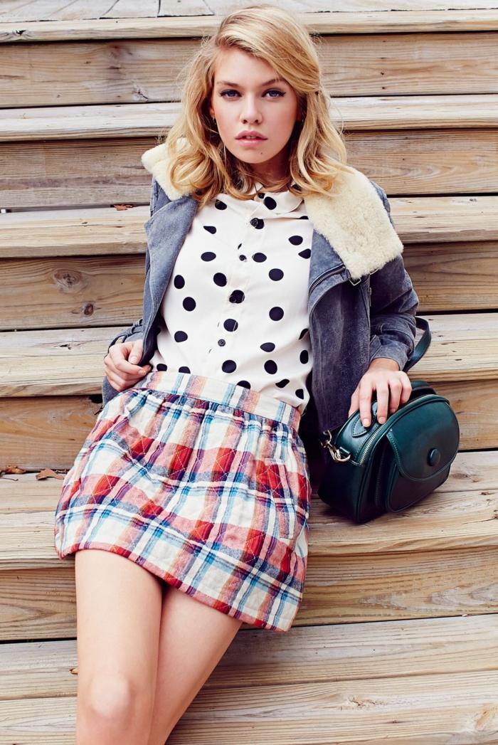 blonde mittellange Haare, karierter Rock, weißes Hemd mit schwarzen Punkten und Jeansjacke, dunkelrgrüne Ledertasche