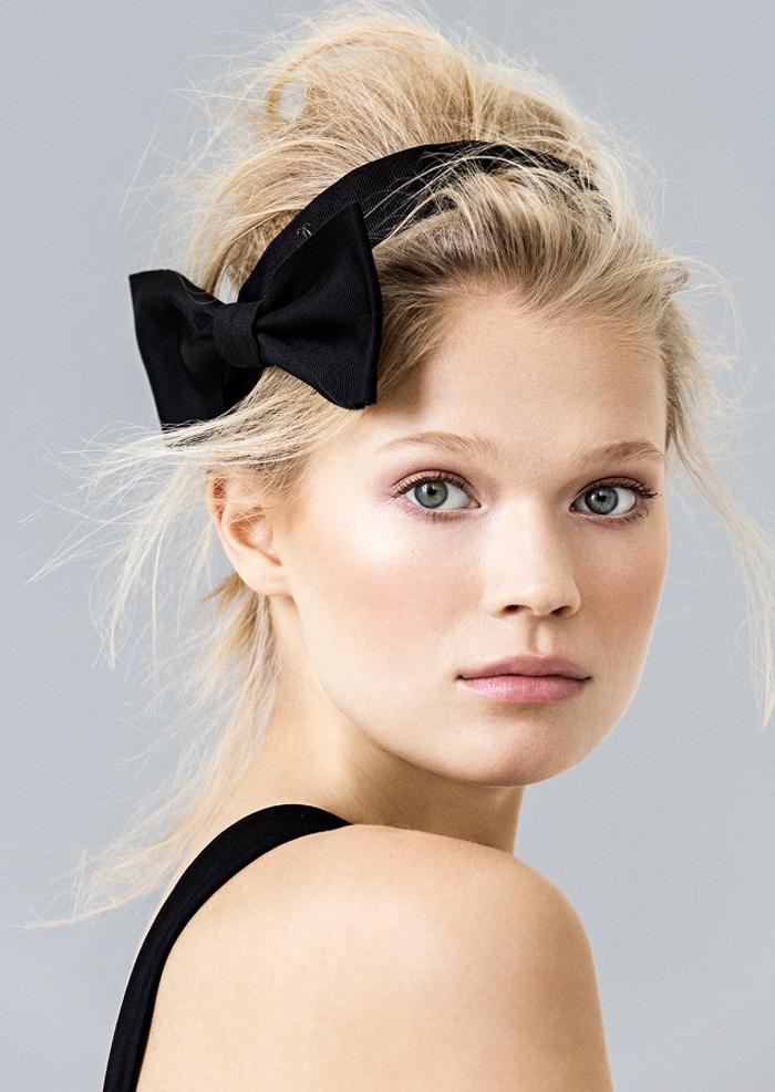 blonde Frau mit schwarzwem Haarband, rosafarbene Lippen und zartes Augen Make-Up, schwarze Träger