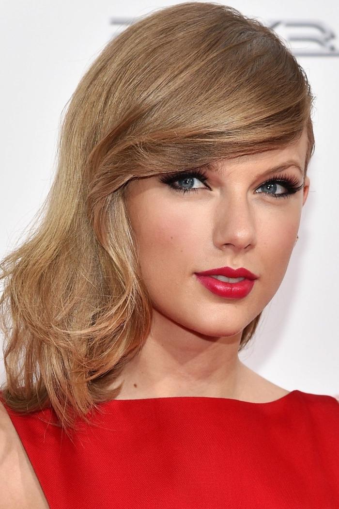Taylor Swift in Rot, hellbraune Haare und blaue Augen, knallrote Lippen und heller Rouge