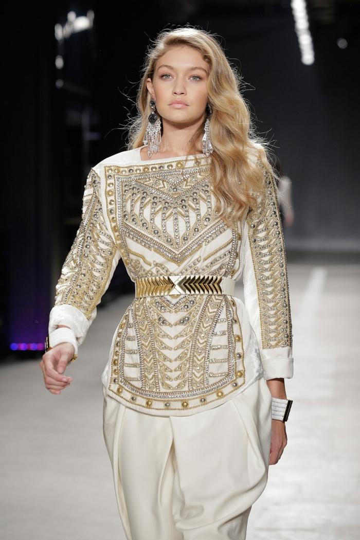 blonde lange Haare mit natürlichen Locken, auffällige Ohrringe, weißer Outfit mit goldenen Perlen