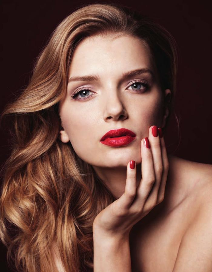 Schöne Frau mit hellbraunen langen Haaren, knallroter Lippenstift und Nagellack, dezentes Augen Make-Up