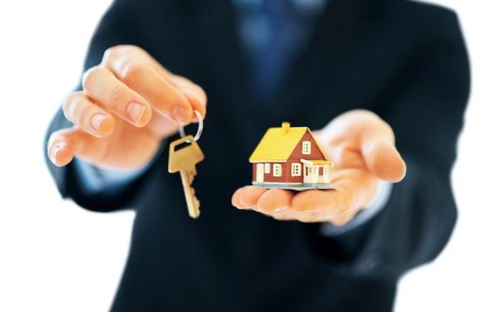 der Immobilienmakler gibt Ihnen Haus und Schlüssel