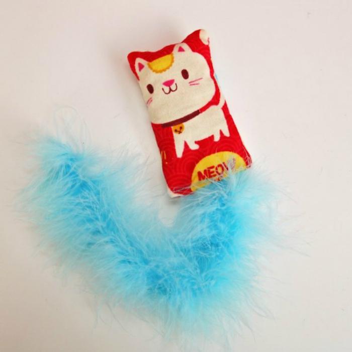 eine weiße Katze als Bild auf einem roten Kissen und einen blauen Band - Katzenspielzeug selber machen