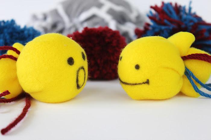 Spiele für Katzen - zwei gelbe Kugeln mit bemalten Gesichtern und viele Pompoms