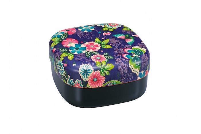 japanische Lunchbox mit bunten Blumen, Schmetterlingen und grünen Baumblättern