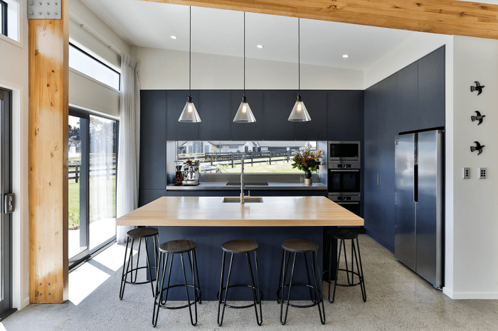 hängelampen über die insel, boden in betonoptik, küche weiß holz und dunkelblau, hölzerne elemente
