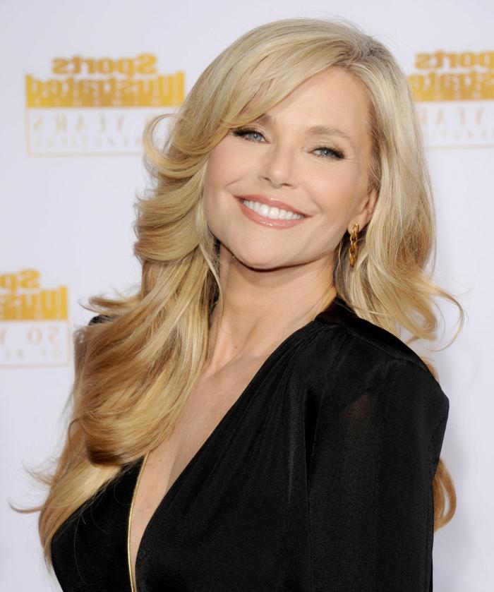 blonde Frau mit schönem Lächeln, dezentes Make-Up, schwarze Bluse mit V-Ausschnitt