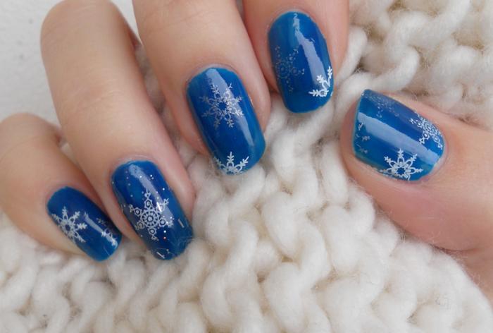 Weiße und silberne Schneeflocken auf dunkelblauem Grund, runde Nagelform, Winter Nageldesign zum Nachstylen