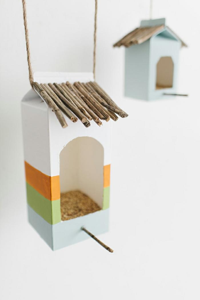 Vogelhäuschen aus Milchkarton selber basteln, mit Samen und Sonnenblumenkernen befüllen, Stäbchen aufkleben