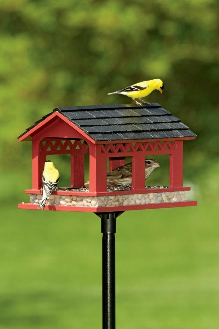 großes rotes Vogelhäuschen, mit Samen und Sonnenblumenkernen befüllt, drei Vögelchen