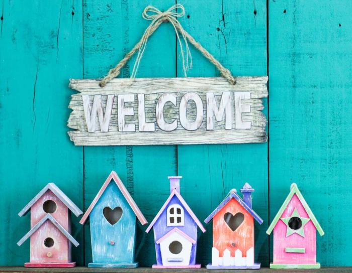 fünf bunte Vogelhäuschen aus Holz, Fenster als Herzen, Willkommen Schild, blauer Hintergrund