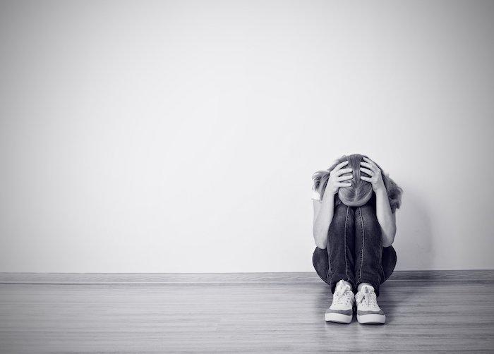 hier ist ein trariges bild mit einer traurigen jungen frau, die weint, und einer großen weißen wand