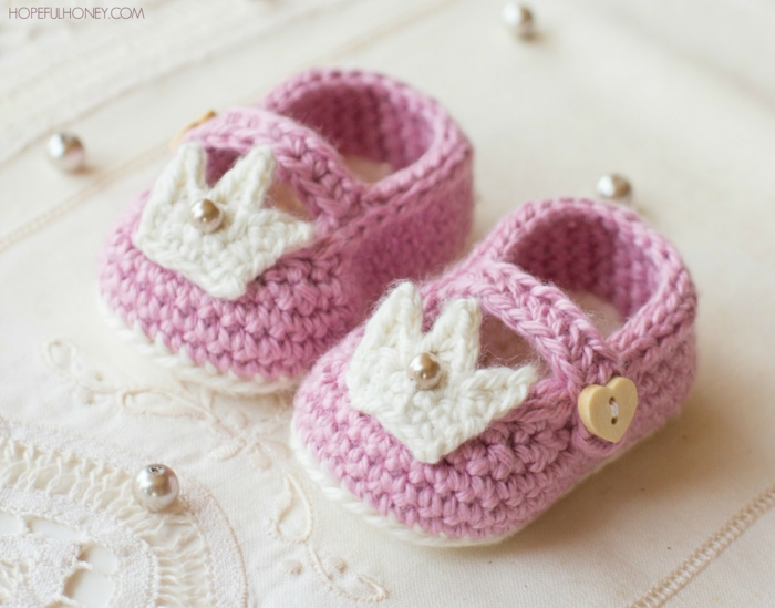 Selbstgestrickte Babyschuhe in Rosa und Weiß, mit Krönchen und Perlen verziert, Herzen-Knöpfe